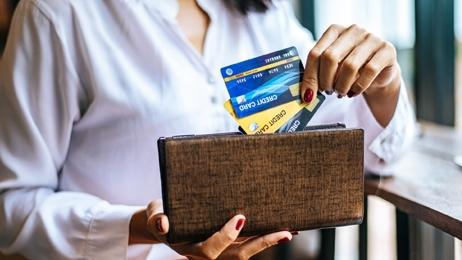 ผู้หญิงถือบัตรเครดิตหลายใบพร้อมกระเป๋าสตางค์สีน้ำตาล