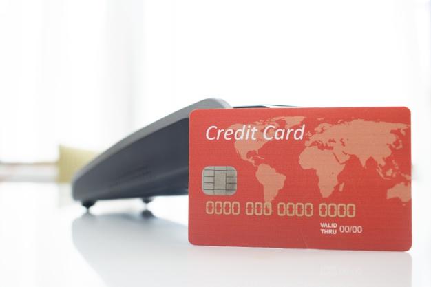 บัตรเครดิตสีแดงพร้อมเครื่องรูดบัตรเครดิต
