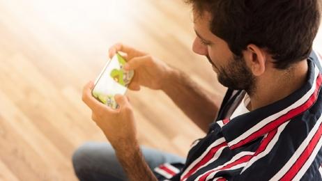 ผู้ชายกำลังนั่งเล่นเกมโทรศัพท์มือถือ