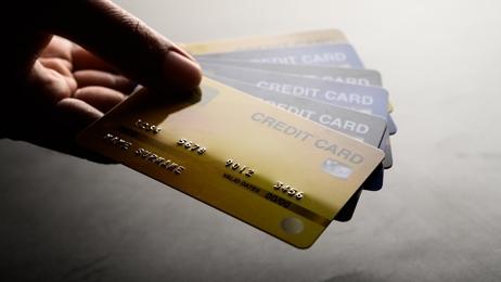 มือกำลังถือบัตรเครดิตอยู่หลายใบ