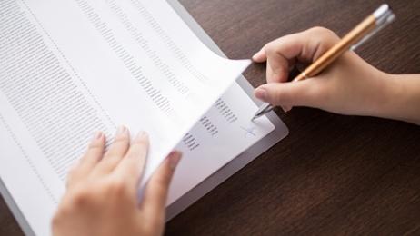 กระดาษเอกสารรายการเดินบัญชีและมือที่กำลังเซ็นต์ชื่อ